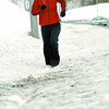 Citizen photo by Brent Braaten Amy Hauk runs up University Way Tuesday afternoon through the deep snow on the sidewalk that was not plowed.
