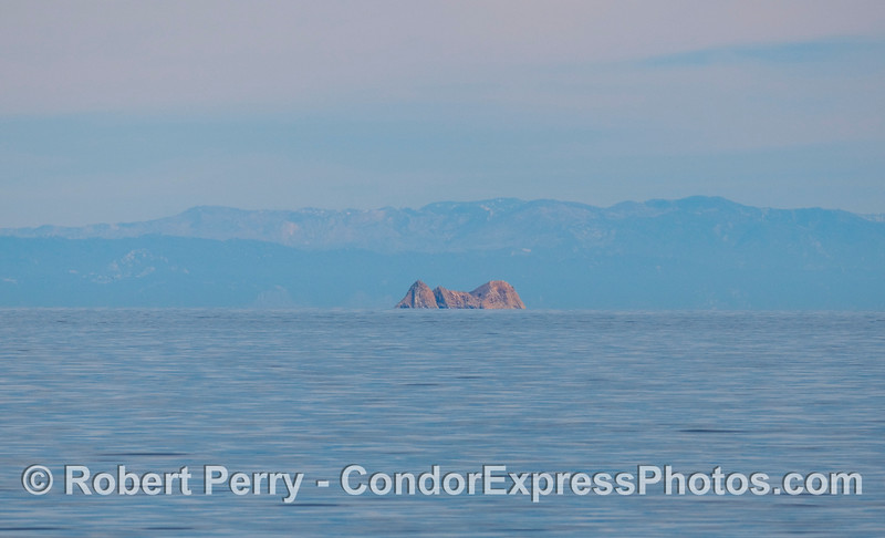 Portrait of Castle Rock, San Miguel Island.  A smooth ocean surface and great visibility.  The Santa Ynez mountains on the mainland can be seen in the background.