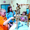 Bryan Meier, 9, left, and Nikki Mueller, 11, Jenna Meier, 9, watch a marble go around a spiral in the Mueller family's Marvellous Mable Machine entry at Westwood Elementary School Wednesday night. Students and their families built contraptions to direct a marble through an obstacle course made with re-useable materials from home. Citizen photo by David Mah