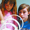Jenna Meier, 9, left, and Nikki Mueller, 11, watch a marble go around a spiral in the Mueller family's Marvellous Mable Machine entry at Westwood Elementary School Wednesday night. Students and their families built contraptions to direct a marble through an obstacle course made with re-useable materials from home. Citizen photo by David Mah