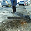 Craig Miller sweeps up the gravel at the enterance to Midas on Victoria Street Wednesday morning. Citizen photo by Brent Braaten