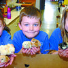 Central Fort George Traditional School grade 1 students Julia Chorney, 6, left, Derian Hannah, 7, and Erin Rushton, 7, show 6 of the chicks that just hatched in the last day. The students had a nice surprise upon returning to Mrs. Krisko's class after Easter. Citizen photo by David Mah