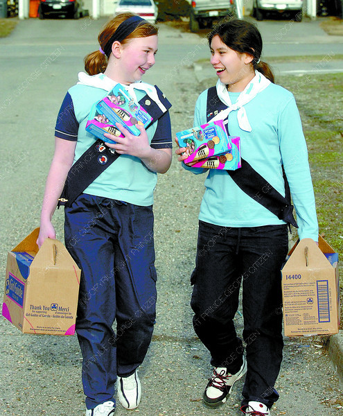 Emily Erickson, 10, left, and Althea Michell, 12, of the 1st South Fort George Girl Guides have a nice chat as they make their way down Wilson Crescent selling cookies. Citizen photo by David Mah