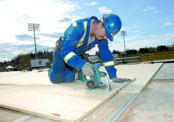 Red Hanson with Chinook Scafolding cuts plywood for the stage at Masich Place stadium in preperation for the Relay for Life that starts at 10 am Saturday morning. Citizen photo by Brent Braaten
