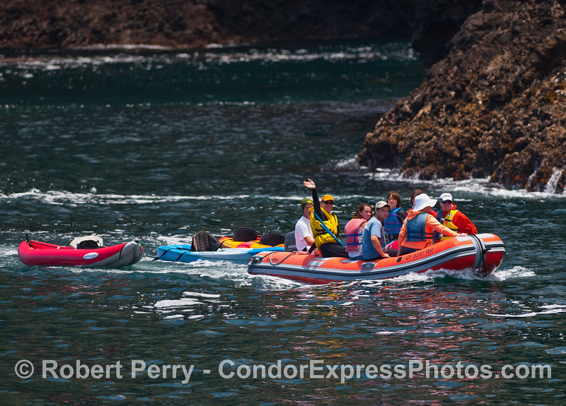 An inflatible boat from the Dive Boat Truth tows kayaks and takes passengers along the steep, rugged north coast of Santa Cruz Island to visit the numerous sea caves.