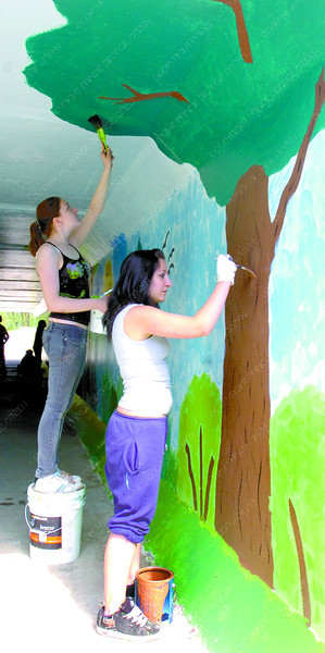 Jodi Slusarchuk, left, Becky Benate, and other students with the Concept Education Program of the Native Friendship Centre paint a forest scene in the Pedestrian Tunnel Mural Project under Highway 16. The Community Policing project should be finished and ready to view Thursday. Citizen photo by David Mah