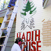 Michael Edward Nardachioni, bottom, and Art Gillmore, paint a totem pole mural on Porter House on Pine Street. The Hadih House Totem Pole represents family, with the eagle protecting family and tree representing environment. Citizen photo by David Mah