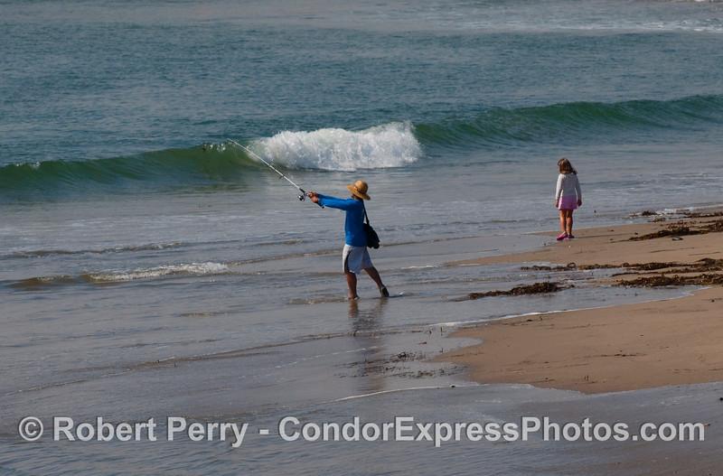 Man fishing on sandspit with young girl - Santa Barbara Harbor.