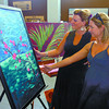 Artist Louise Busse, left, and Melissa Bennett, view Busse's paintings at Homework Wednesday evening. Other displays were at the store including more art and a yoga demonstration. Citizen photo by David Mah