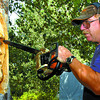 Chainsaw woodcarver John Rogers, owner of JR's Exotic firewood, carves a face in a tree at the Southpark RV Park on Highway 97 south. Rogers carves all sizes of animals there. Ciitzen phoho by David Mah