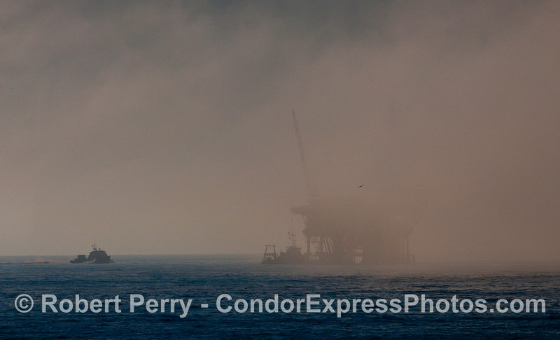 A fog bank envelopes an offshore oil platform and support boats.