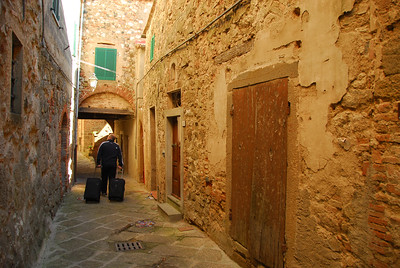 Patrick pulling the cases across the stone streets of Roccatederighi