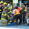 City of Prince George Firefighters and BC Ambulance paramedics tend to the rider of a scooter that was involved in a crash with a car at Victoria Street and 3rd Avenue Thursday afternoon.  Citizen photo by Brent Braaten