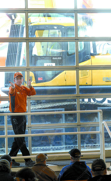 Jamie Fraser, with Ritchie bros. Auctions carches bids during the fall auction at their site on Highway 16 East Thursday. Over 1,000 bidders were registered for the auction that had more construction type equipment then other auctions.  Citizen photo by Brent Braaten
