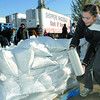 Erin Wakabayashi a Duchess Park student wraps up a pallet of sandbags at Shoppers wholesale Saturday morning. Duchess Park students from the band program and Me to We (leadership class) were filling the sand bags as a fundraiser. Shoppers has been paying  groups to fill sand bags, as a fundraisering event, for the last 5 years.  Citizen photo by Brent Braaten