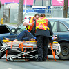 BC Ambulance attendants take a female driver to hospital after a two vehicle crash at 1st Avenue and Queensway just after 9 A.M. Wednesday morning. An assistant with the opening of the door stands by. A pickup in the initial crash struck another parked pickup. Citizen photo by David Mah