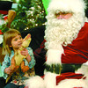 Sarah Robinson, 4, shows Santa her 'Biggest T-Rex in the Universe' during her Christmas picture with Santa at the Pine Centre centre court Wednesday. Citizen photo by David Mah