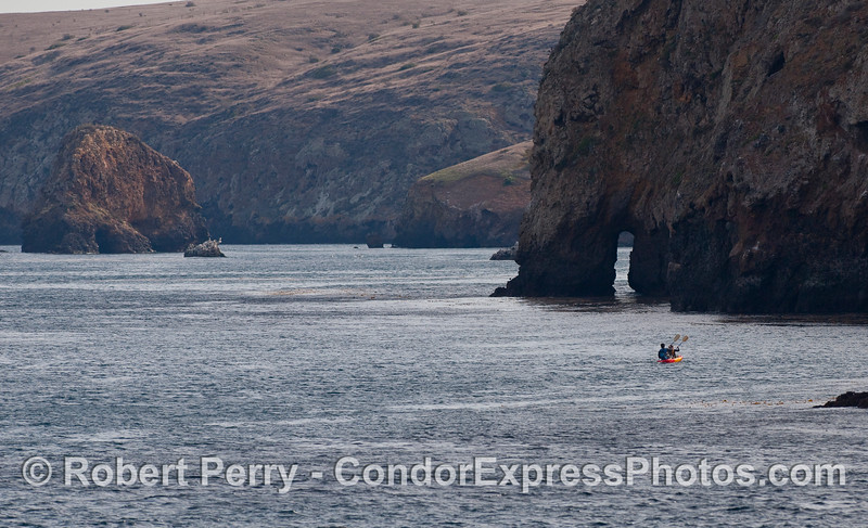 Kayakers explore the sea caves and arches along the northern side of Santa Cruz Island.