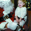 Autumn-Lee Wanless, 2, has a chat with Santa  during the 7th Annual Child Care Association Christmas breakfast, she finally gave up on her utensils and used her hands. About 125 children attended the event held at the Salvation Army on Ospika. All the daycares participating in the breakfast also brought donations of childrens items and food to the salvation Army.  Citizen photo by Brent Braaten