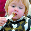 Jack Tidsbury, 2, has a close look at his sausage during the 7th Annual Child Care Association Christmas breakfast, she finally gave up on her utensils and used her hands. About 125 children attended the event held at the Salvation Army on Ospika. All the daycares participating in the breakfast also brought donations of childrens items and food to the salvation Army. Santa clause also maid an apperance.   Citizen photo by Brent Braaten
