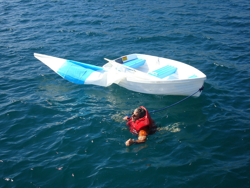 Forrest swimming the sailing dinghy back to Stepping Stone after the rudder came apart