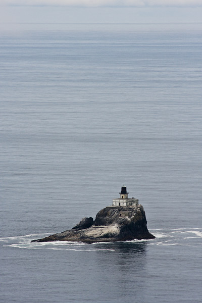 The loneliness of the ocean isolates this lighthouse on its rock a short distance from shore.