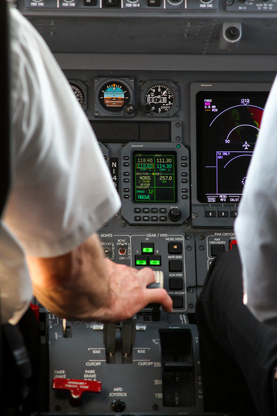 Our pilot works the throttle of the Lear Jet carrying us from Anchorage to Portland.