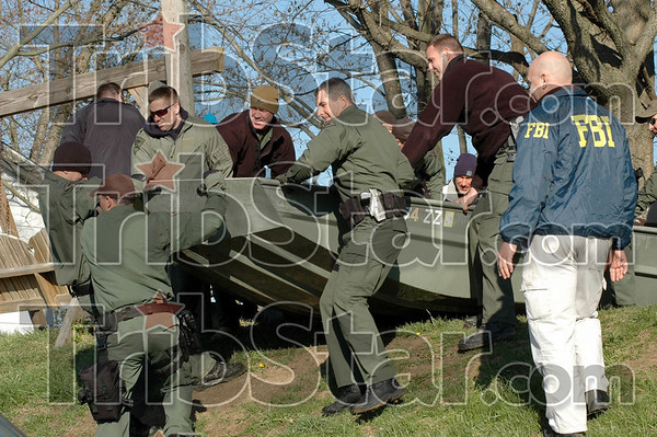 Water craft: State Police officers prepare to load a water craft after using it to approach three homes in southwestern Vigo Co. by river Thursday morning.