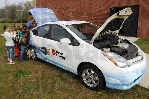 Hybrid: Meadows Elementary School kids listen to Rick Burger of Duke Energy as he explains how the plug-in electric vehicle manages to get 70 miles per gallon of gas during Thursday Green Day at the school.