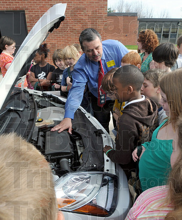 How it works: Rick Burger of Duke Energy explains how a plug-in electric vehicle works to a group of Meadows Elementary School kids during Thursday's Green Day event.