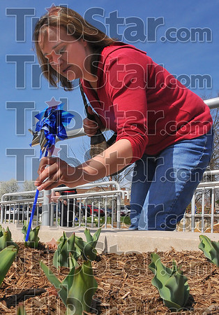Planting prevention: Charlotte Fulk plants a pinwheel in the flower garden outside the Vigo County Public Library early Thursday afternoon.