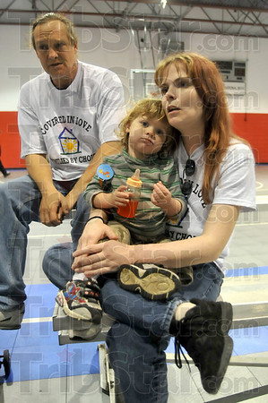 Tribune-Star/Joseph C. Garza<br /> Tough times: Carin Morin, right, holds her son, Dominic, as she talks Sunday at Ryves Hall about the difficulties she and her husband, Phil Morin, left, faced after they were burned out of their apartment in March.