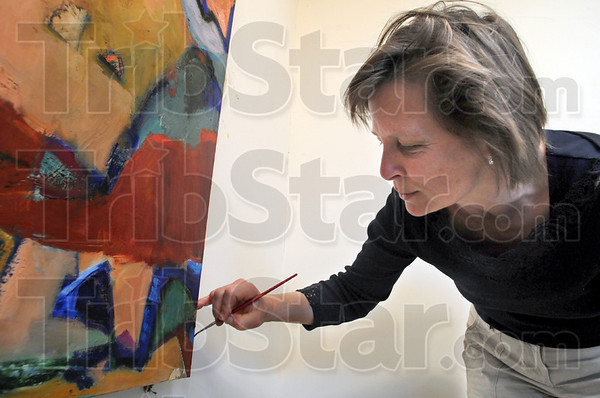 Touch-up: Mary Kramer does some minor touch-up on a print she's preparing for a client Saturday afternoon in her studio.