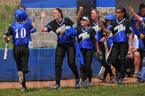 Enough: Steph Robinsonm is greeted at the dugout by teammates after she scored  the first run against Evansville. The Sycamores, behind Darcy Woods' shutout pitching won 3-0.
