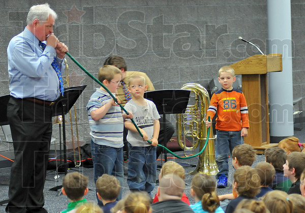 Hose-a-phone: Randy Mitchell uses a garden hose and the mouthpiece from his trombone to get a point across to the Turkey Run Elementary School students Friday afternoon. Assisting in the project are Josiah Norman, Shane Carter and Gavin Johnston, students in Alisha Leonard's class.