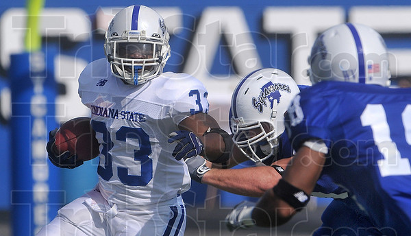 Tribune-Star/Joseph C. Garza<br /> Full speed spring game: Indiana State running back Antoine Brown (33) tries to escape two incoming defending teammates, including defensive back Larry Carter, right, during the annual Blue/White spring game Saturday at Memorial Stadium.