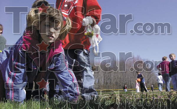 Tribune-Star/Joseph C. Garza<br /> Cheyenne Fennell, 10, tries to find one of the last grand prize eggs left on Wilson Field during the Prairie Creek Lions Club's fourth annual Easter Egg Hunt Saturday off of Bowen Drive.