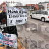 Tribune-Star/Joseph C. Garza<br /> Protest and honk: Philip Haverly wears a President Obama mask as he holds up a sign on a median on Third Street Wednesday across from a tea party demonstration on the front lawn of the Vigo County Courthouse.