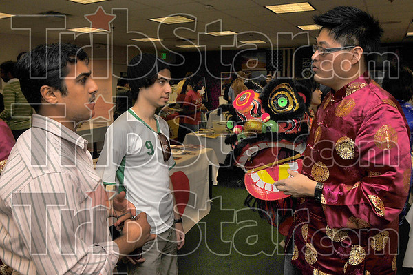 "Power and good luck: Saudi Arabian students Abdullah Alkamis and Thaier Alawadh learn about the lunar new year from Raccoon Kuo of the Taiwanese Students Association. They were at Union Hospiptal's ""Colors of Our Community Cultural Fair"" Wednesday morning."