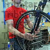 Full service: Jerry Harnack, owner of J's Bikes, sets a front wheel on a bike he has serviced.
