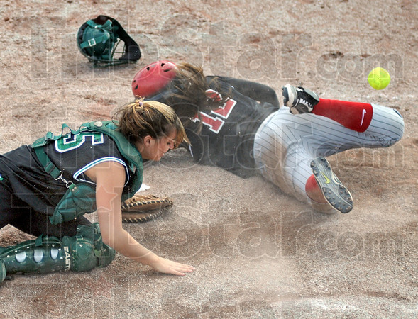 Score: South's #12, Macy Toon slides across home plate head-first to score as the throw gets away from West Vigo catcher #25, Brianna Stewart during Wednesday's game.