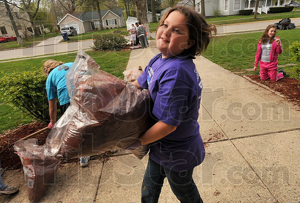 Tribune-Star/Joseph C. Garza<br /> Mulch muscles: Farmersburg Elementary School fifth-grader Ariel Alcorn uses her muscles to carry a bag of mulch to a spot on the front lawn of the school Wednesday. Alcorn and her fellow classmates were doing their part to improve the school grounds for Earth Day.