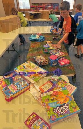 Generous hearts: The students of Riley Elementary School Gathered about $500 worth of games and toys for school children in the Congo. The toys will be shipped in a container used to take a portable sawmill to the central African country. On the right of the table is Landon Ellis who initiated the project at the school.