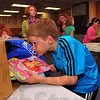 Congo bound: Riley Elementary School fifth grader Matthew Green slides coloring books into a box bound for the Congo. Students gathered about $500 worth of toys and games for their counterpats in the third world country.