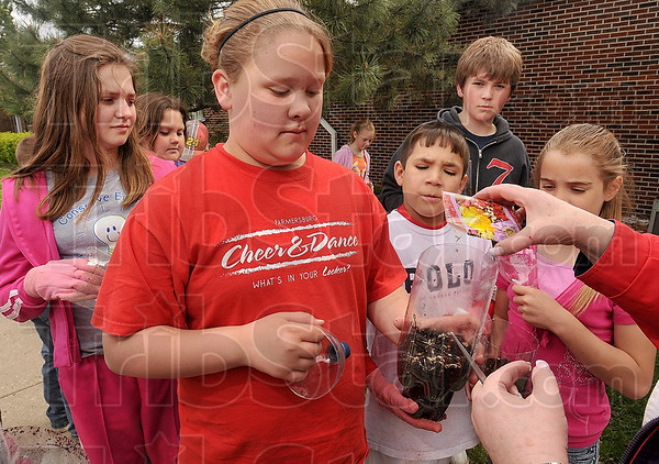 Tribune-Star/Joseph C. Garza<br /> Poster contest finalist: Farmersburg Elementary School fifth-grader Samantha Thomas holds her terrarium for teacher, Gail Nattkemper, as Nattkemper pours in seeds Wednesday at the school. Thomas was named a finalist in a national poster contest sponsored by the North American Marine Environment Protection Association and Immersion Learning.