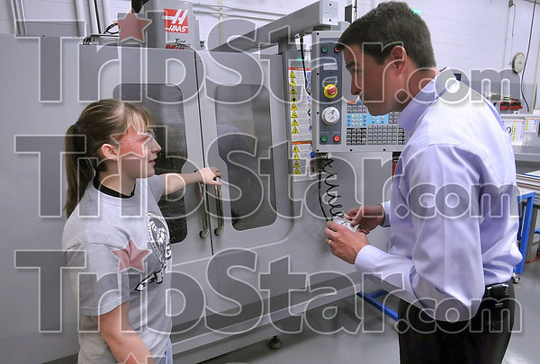 Tribune-Star/Joseph C. Garza<br /> Cutting technology: Terre Haute South junior Amber Bailey describes to Congressman Brad Ellsworth how a Haas mill machine works as he holds an intricately machined part she made Monday at the school.