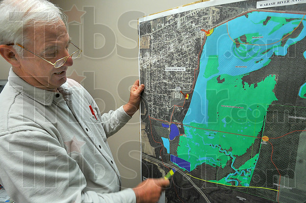 Overview: Keith Ruble, superintendent of the Vigo County Parks Department, looks over an aerial photograph with graphics that show plans for the wetlands and the levee trail east of West Terre Haute.