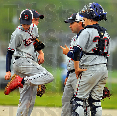 Sticky situation: Terre Haute North head baseball coach Shawn Turner, second from right, talks with pitcher Sebastian Mundy(cleaning mud from his cleats), first baseman Jared Eller and catcher Doug Collett.