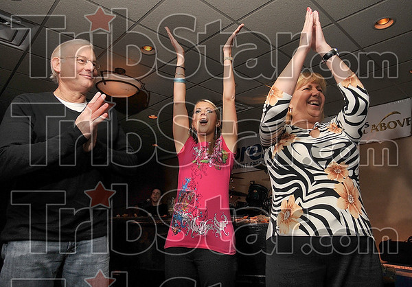 Tribune-Star/Joseph C. Garza<br /> A hand clapping good time: Larry Kirchner, Tasha Fagg, and Jenny Patterson lead their side of the room through a portion of a song during the Howl at the Moon fundraiser Monday at the Ohio Building.
