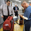 Game Ready: Dr. Andy McDonald (L) and Pat Board watch as Dr. Gary Ulrich prepares the Game Ready system for demonstration at the Vigo Co. School Corp. Thursday afternoon.